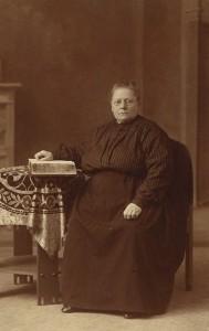 Een streng ogende Vrouw Vonk met haar hand op de Statenbijbel